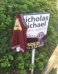 Sold house sign, with She Moves jacket